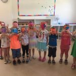 10 kids wearing masks they made at summer camp