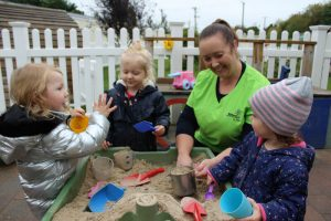 one teacher and three toddlers playing with sand box