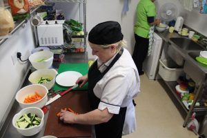 chef cutting vegetables in the kitchen of mullingar montessori and the den after school care