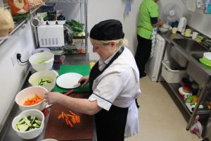 chef in kitchen chopping vegetables at mullingar montessori and the den after school care
