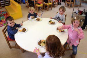 five small children eating their dinner