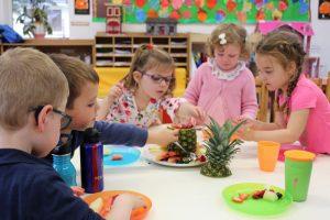 five montessori children enjoying a fruit snack