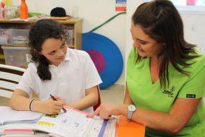 girl doing homework with teacher