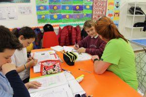 three kids doing homework with teacher