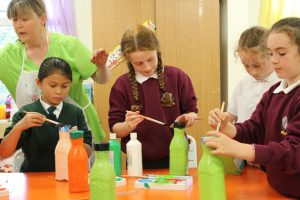 children painting bottles green