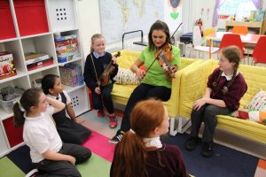 children watching teacher play the violin