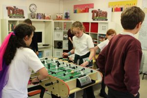 two girls playing table football at the den after school club