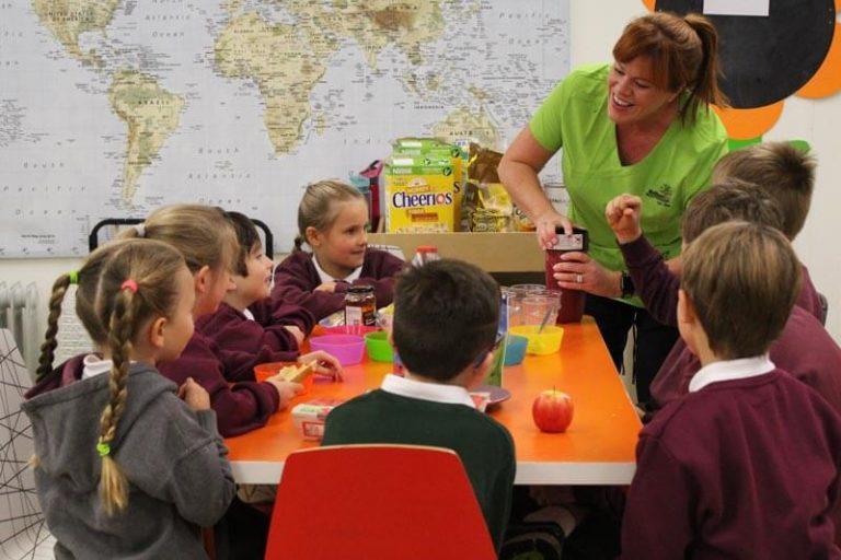 school kids eating breakfast before school with adult