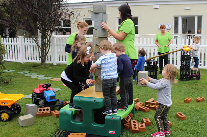 mullingar montessori schools kids playing in garden building with play blocks