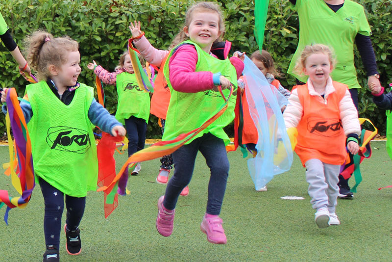 kids carrying colourful ribbons running