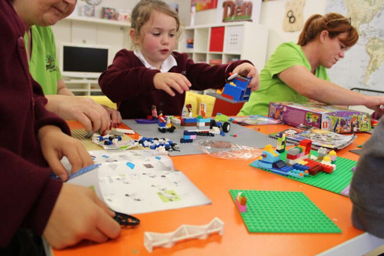 girl and teacher playing with lego