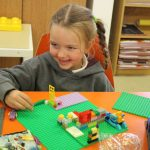 girl playing with lego after school