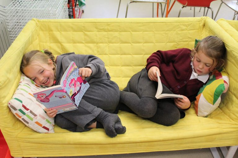 two girls reading on a yellow couch at after school care mullingar the den