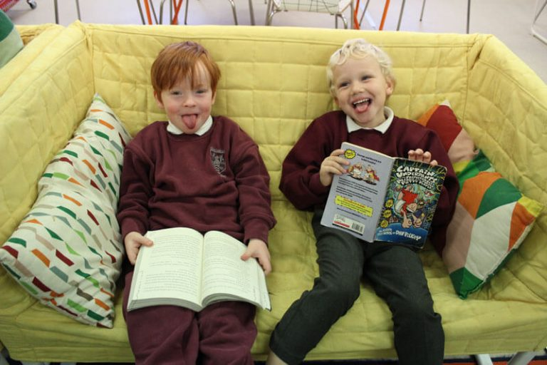 two boys reading on a yellow couch at after school care mullingar the den