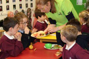 teacher handing out fruit to pupils