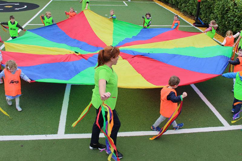mullingar montessori school kids playing outside with parachute