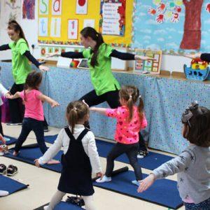 three teachers demonstrating yoga poses to class of children