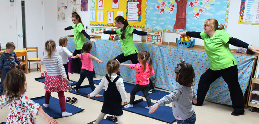 three teachers demonstrating yoga poses to class of children